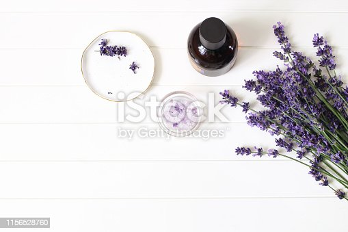 Styled summer beauty composition. Essential, massage oil, lavender flowers bouquet, bath salt on white wooden table background. Organic herbal cosmetics, spa concept, empty space, flat lay, top view