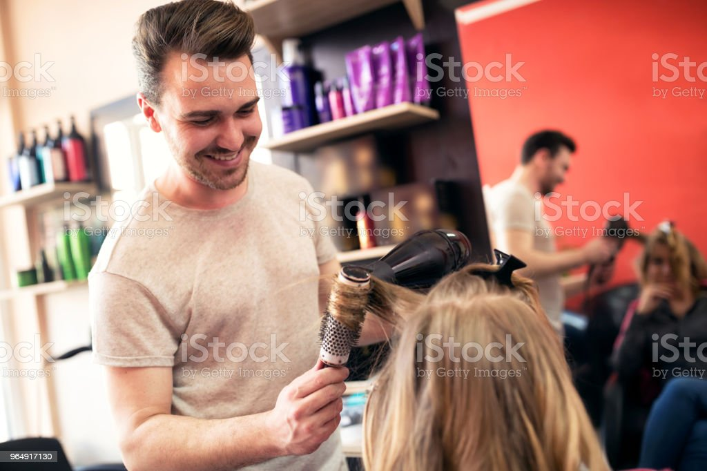 Styling hair by male hair stylist at beauty salon royalty-free stock photo