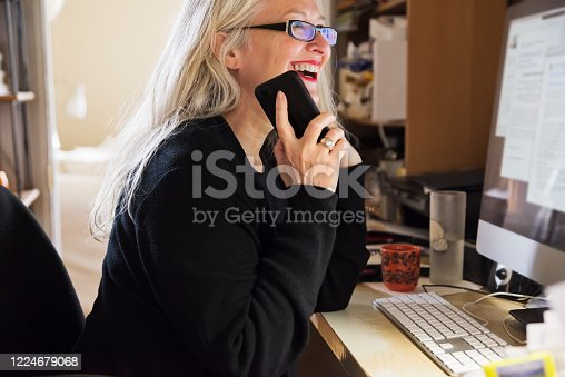 Stylish 50+ woman working from untidy home office. She has long white hair and is wearing black casual clothes and red lipstick. She is using a computer and a mobile phone. Horizontal waist up indoors shot with copy space.