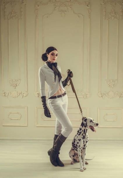 stilvoll, ein jäger in einem weißen vintage-kostüm pferdefrau mit hohen lederstiefeln. dame behandelt den dalmatinischen hund. mädchen mit einer stilvollen strengen frisur - königin kopfteil stock-fotos und bilder