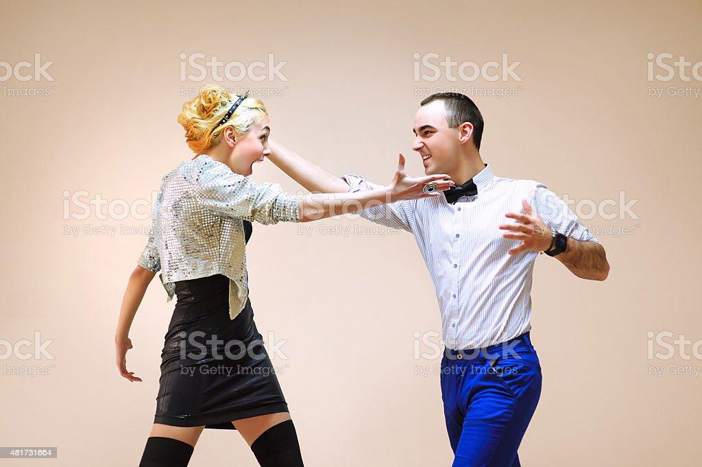 Stylish adult girl with guy, simulating funny battle on  background stock photo