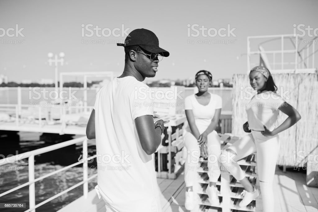 Stylish african american boy, wear on white clothes, glasses and cap, with mobile phone at hands, against two girls. Street fashion of young black people. 免版稅 stock photo