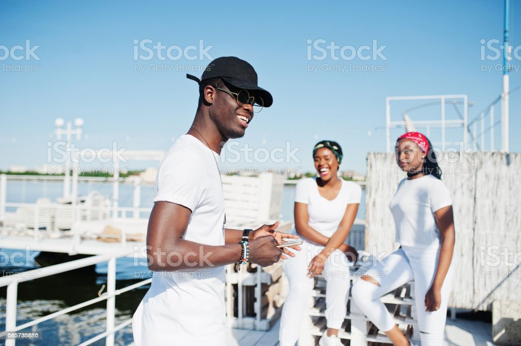 Stylish african american boy, wear on white clothes, glasses and cap, with mobile phone at hands, against two girls. Street fashion of young black people. royalty-free 스톡 사진