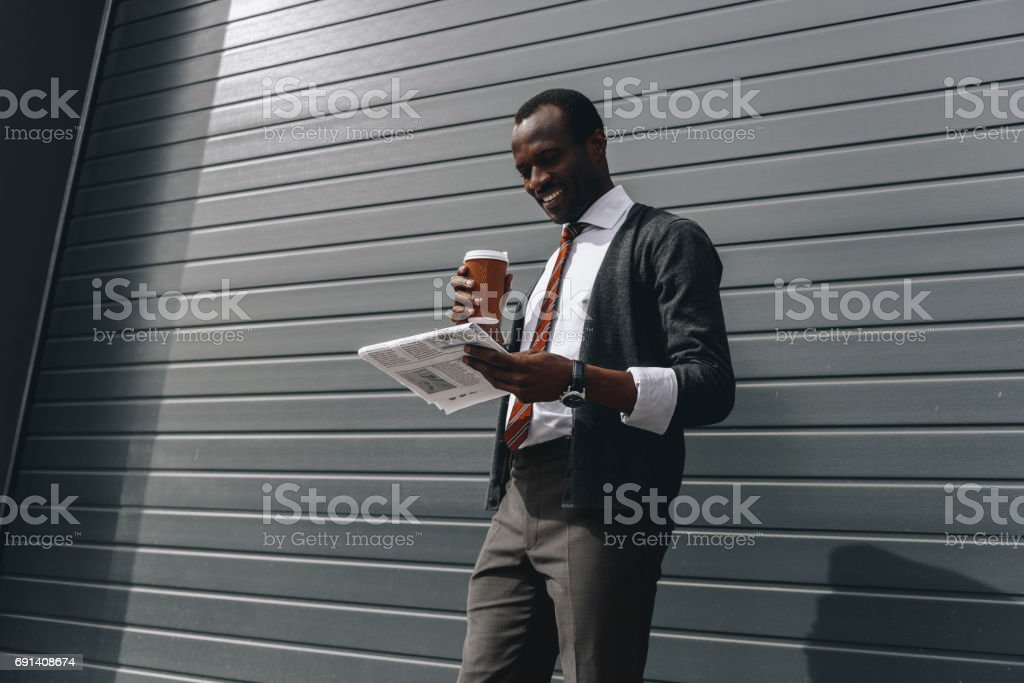stylish african american businessman reading newspaper and holding coffee to go outdoors stock photo