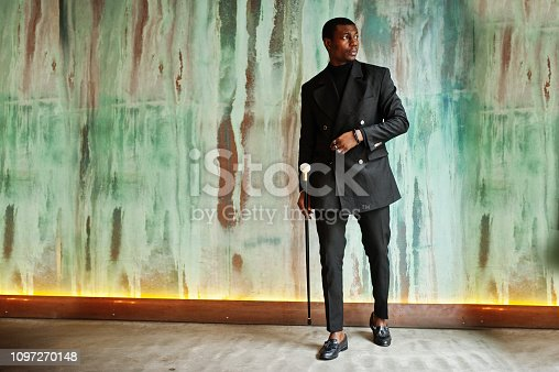 Stylish african american gentleman in elegant black jacket, holding retro walking stick as cane flask or tippling cane with golden diamond ball handle. Rich fashionable afro man against green wall.