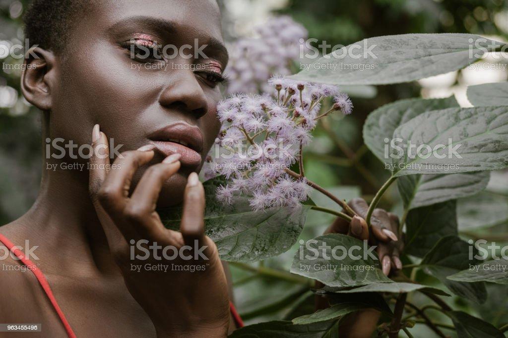 élégante femme afro-américaine avec paillettes, ombres à paupières en posant avec fleurs - Photo de A la mode libre de droits
