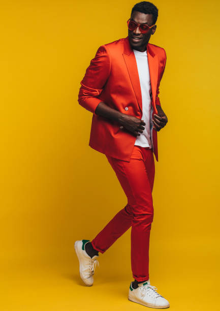 Stylish african man Full length of stylish young african man in orange outfit over yellow background. Fashion model in smart casuals. jacoblund stock pictures, royalty-free photos & images
