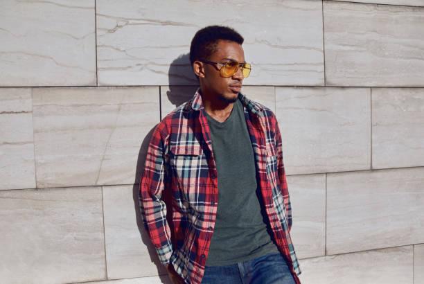 stylischer afrikanischer mann trägt rotes plaides hemd, wegschauen, kerl posiert auf der stadtstraße, grauer backstein-hintergrund - vogue muster stock-fotos und bilder