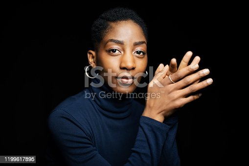 Portrait of attractive african woman looking at camera. Close-up of african female with short hair wearing turtle neck t-shirt against black background.
