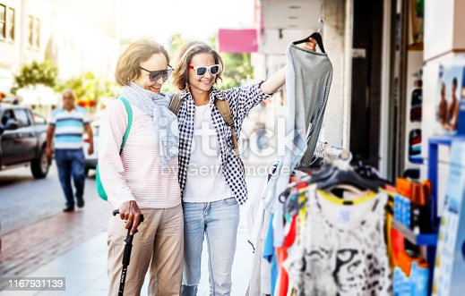 Stylish and beautiful mature mother and adult daughter travel together, walk along the street and shopping. Family, travel, shopping, joy, communication, street market