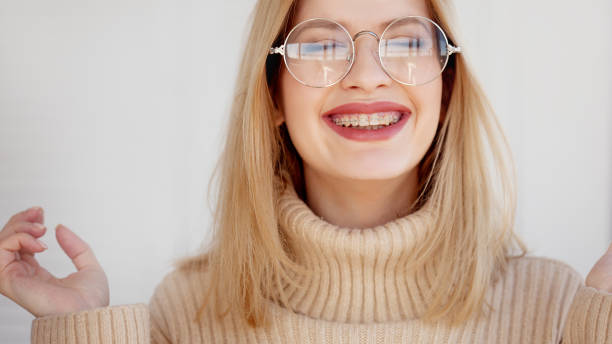 stylisch und schön junge blondine mit brille und beigefarbenem überflusspullover. - kieferorthopäde stock-fotos und bilder