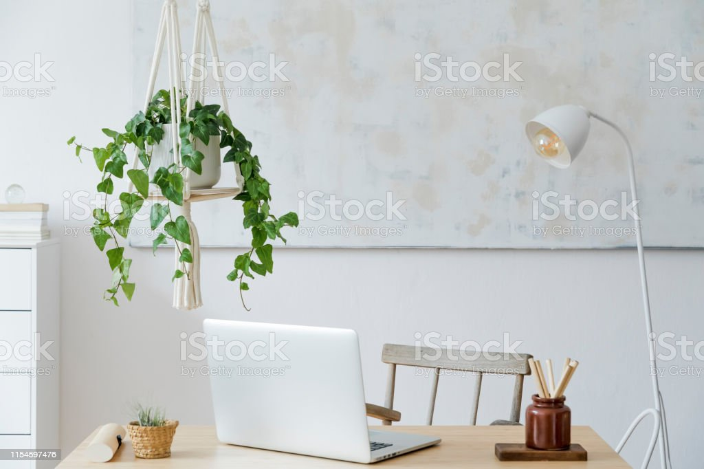 Stylish And Boho Home Interior Of Living Room With Wooden Desk Laptop White Lamp Macrame Shelf And Desk Supplies Design And Elegant Accessories Modern Home Decor Abstract Painting On The Wall Stock