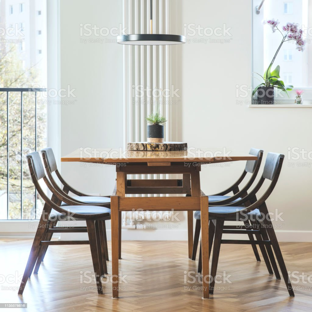 Stylish And Cozy Dining Room Interior With Design Family Table Chairs And Lamp Big Sunny Windows White And Yellow Marble Walls And Brown Wooden Parquet Modenr Space Stock Photo Download Image