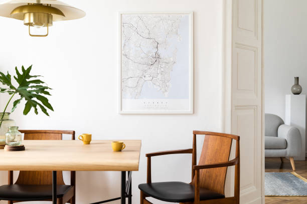 Stylish and eclectic dining room interior with mock up poster map, sharing table design chairs, gold pedant lamp and elegant sofa in second space. White walls, wooden parquet. Tropical leafs in vase. stock photo
