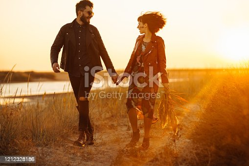 Photo. Enjoying time together. Stylish and loving couple enjoying each other by the sea. The couple is young and in love. The concept of youth, love and lifestyle. Beautiful sunset on a summer day.