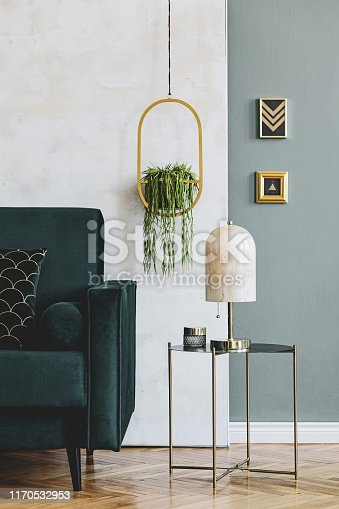 Design composition of living room interior with green vlvet sofa and elegant accessories. Modern home decor. Template.