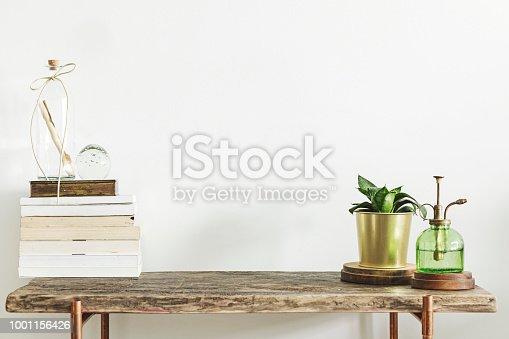 istock Stylish and modern decor with wooden console, books, plants and accessories. Copy space for inscription. 1001156426