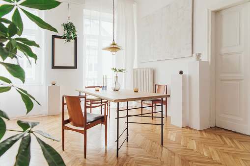 Stylish and modern dining room interior with design sharing table, chairs, gold pedant lamp, abstract paintings and elegant accessories. Tropical leafs in vase. Eclectic decor. Brown wooden parquet.