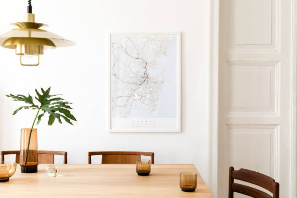 Stylish and modern dining room interior with mock up poster map, sharing table design chairs, gold pedant lamp and cups of coffee. White walls, wooden parquet. Tropical leafs in vase. Eclectic decor. stock photo