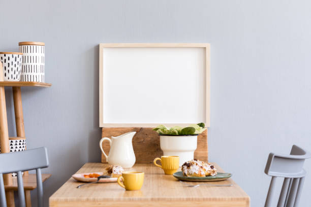 Stylish and modern interior of kitchen space with small wooden table with mock up photo frame, plants, design cups, furnitures and tasty dessert. Scandinavian room decor with kitchen accessories. stock photo