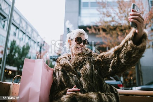 A fun and cheerful senior woman enjoys a day out on the town in the city of Portland, Oregon.  She wears fashionable clothing with a bit of flair and playfulness.  She takes a selfie with her smartphone to share on social networks.