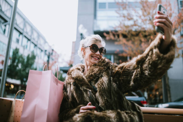stylish and quirky senior woman takes selfie - photo messaging stock photos and pictures