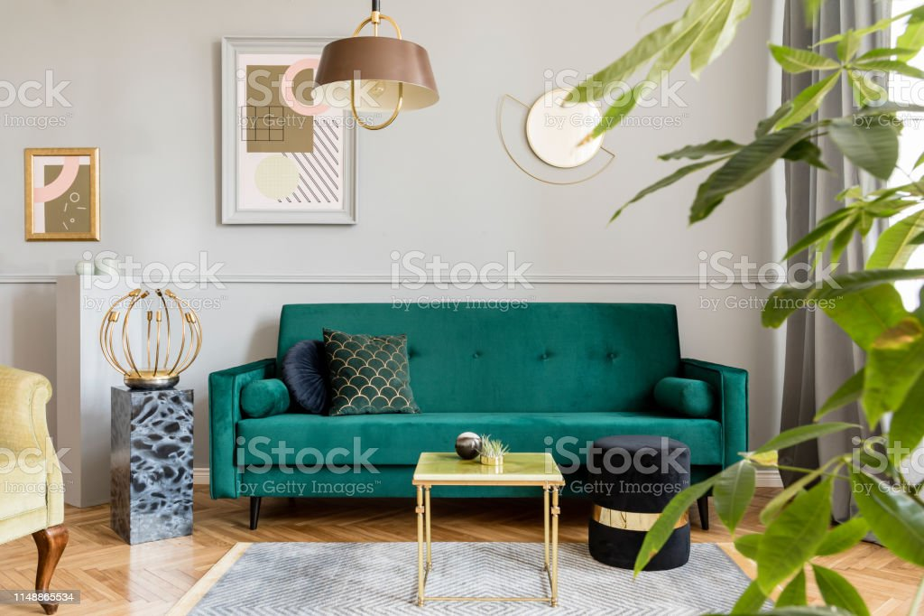 Stylish And Tasty Living Room Of Apartment Interior With Elegant Green Velvet Armchair And Sofa Marble Table Design Lamp And Chic Accessories Abstract Paintings On The Gray Wall Luxury Home Decor Stock