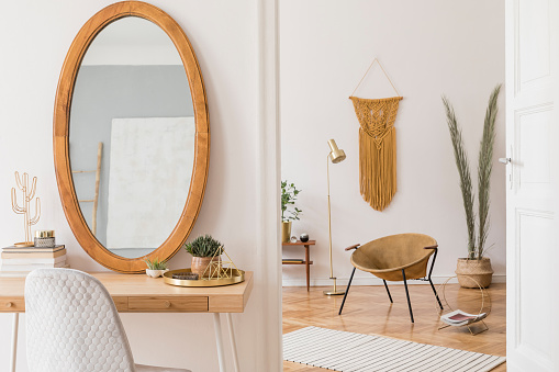 Stylish and warm interior of apartment studio with gold armchair, wooden mirror, design furnitures and accessories, plants, lamp and big macrame on the white wall. Modern home decor of living room.