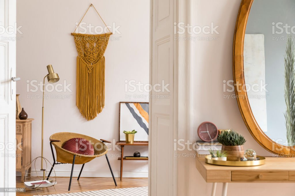 Stylish And Warm Interior Of Apartment With Gold Armchair Wooden Mirror Frame Design Furnitures And Accessories Plants Gold Lamp And Macrame On The White Wall Modern Home Decor Of Living Room Stock