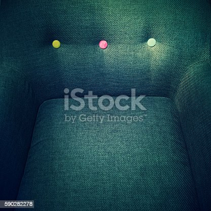 Close-up of a stylish armchair with colorful decorative buttons.