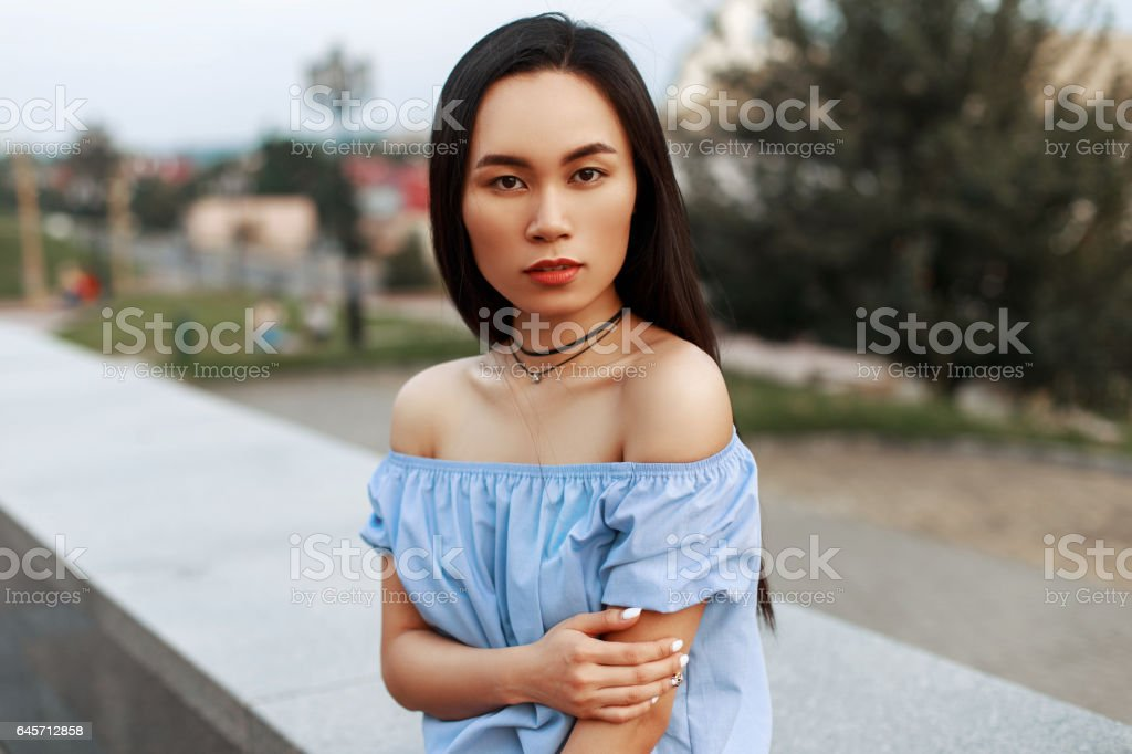 Stylish Asian beautiful girl in blue blouse posing on the background of the city. stock photo