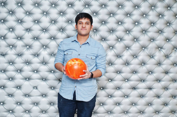 Stylish asian man in jeans shirt standing with bowling ball at hand against silver wall background. stock photo
