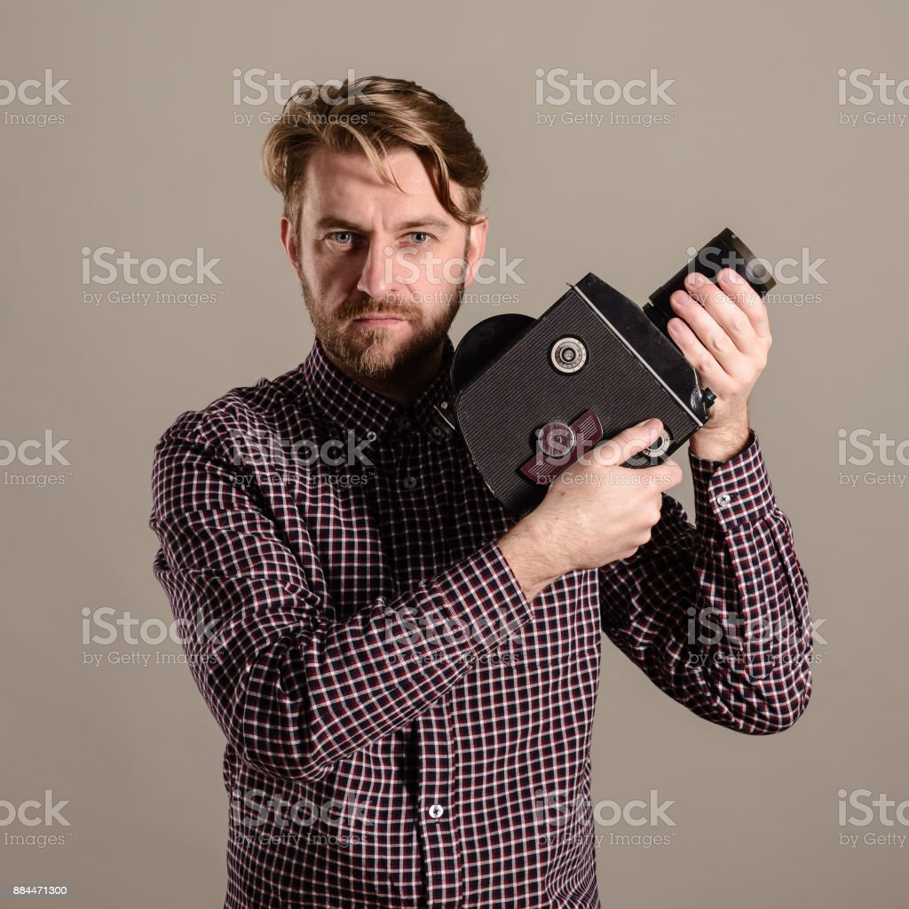 Stylish attractive cameraman in a checkered shirt holds in the hands of an old movie camera stock photo