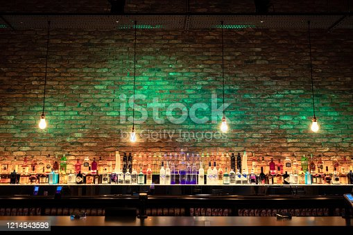 Wide angle shot of a bar counter and shelves of alcohol behind the bar.