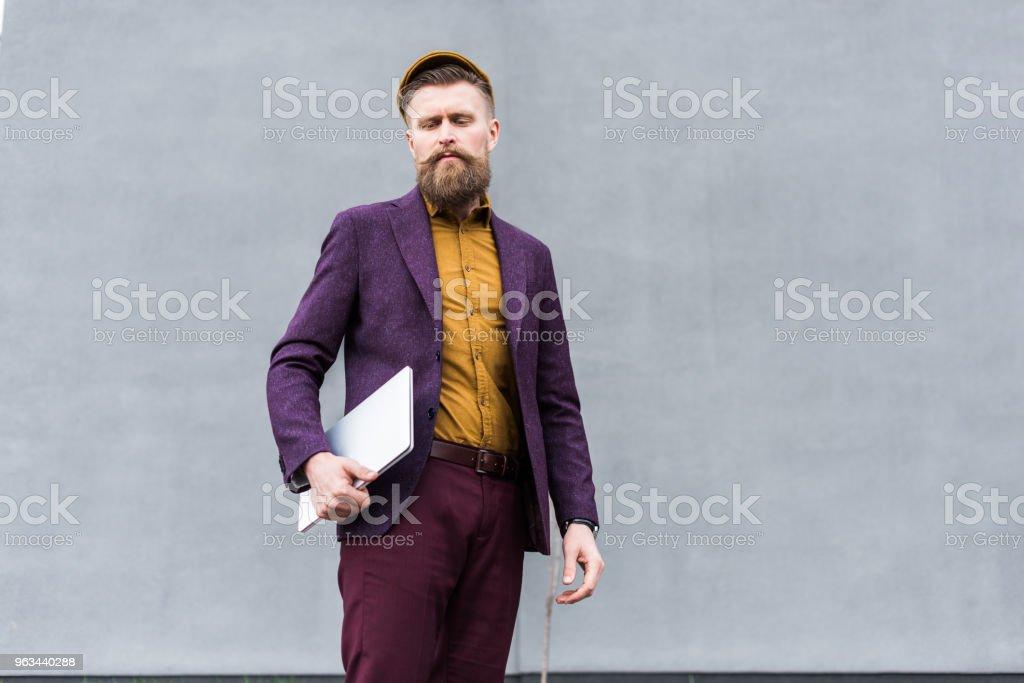 Stylish bearded businessman standing with laptop - Zbiór zdjęć royalty-free (Biznes)