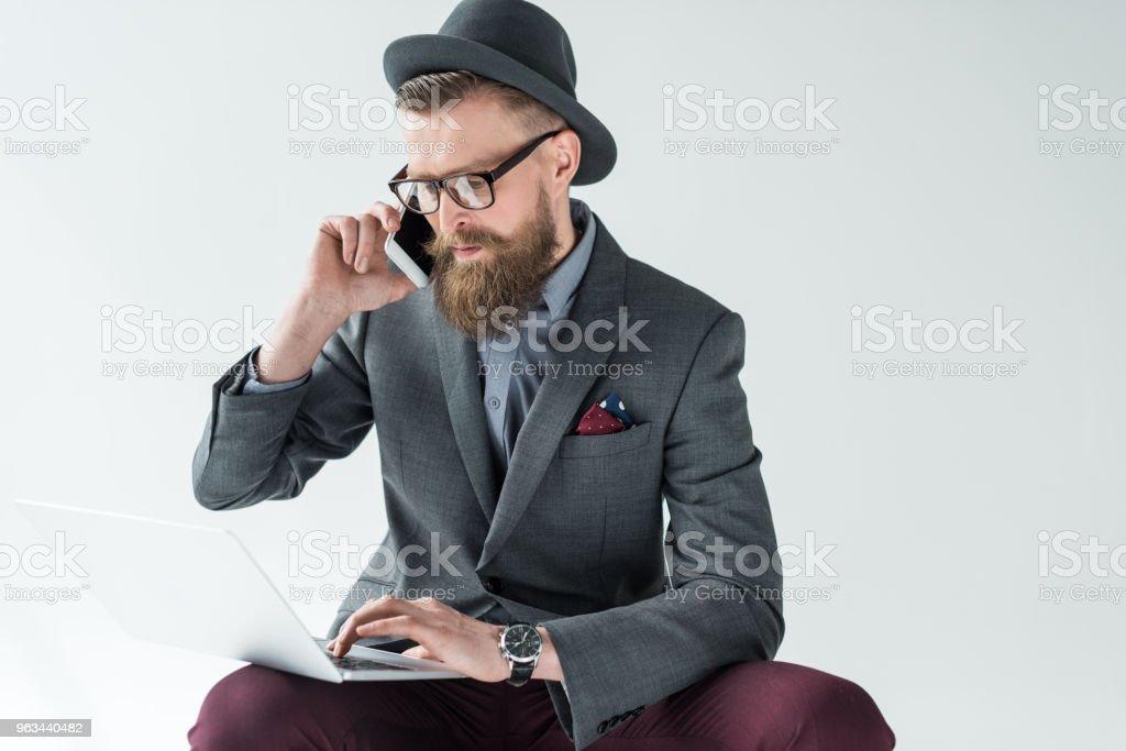 Homme d'affaires Barbu élégant parler sur smartphone et travaillant sur ordinateur portable isolé sur fond clair - Photo de A la mode libre de droits