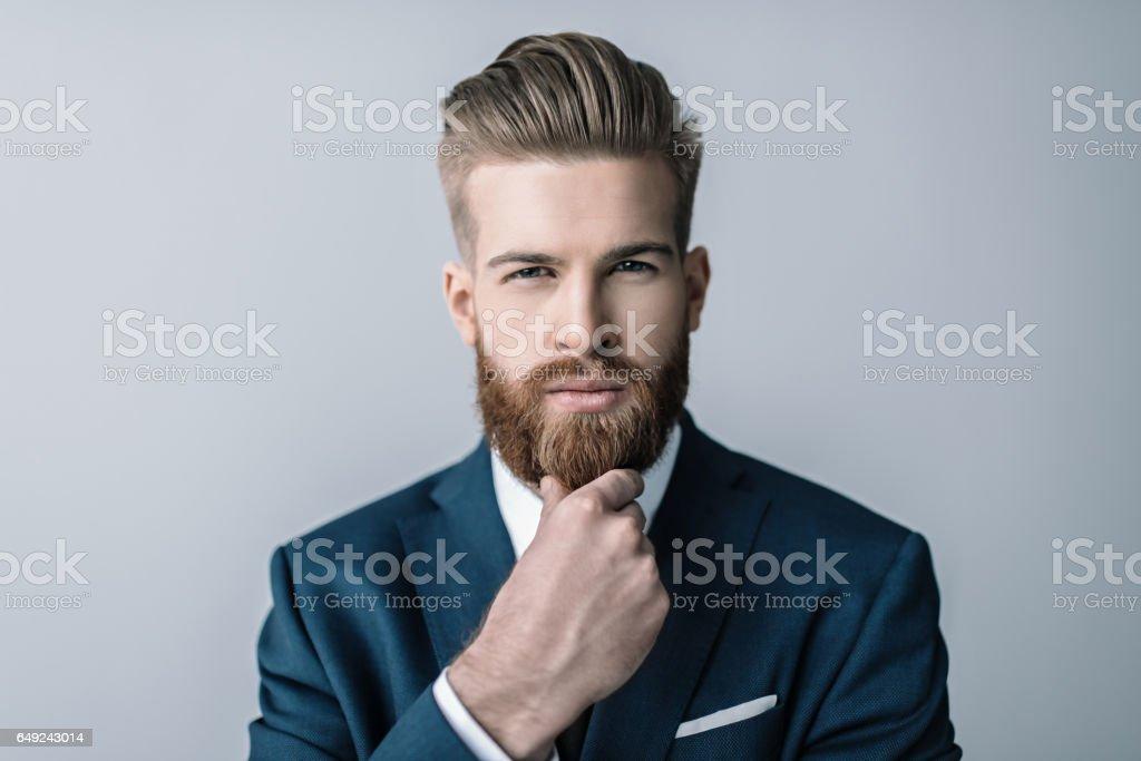 Elegante empresario barba con la mano en el mentón mirando a cámara - Foto de stock de A la moda libre de derechos
