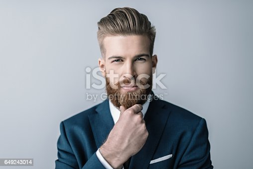 istock Stylish bearded businessman with hand on chin looking at camera 649243014