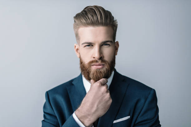 stylish bearded businessman with hand on chin looking at camera - beard stock pictures, royalty-free photos & images