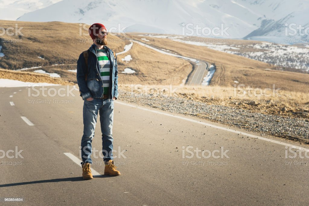 A stylish bearded hipster in sunglasses with a vintage backpack stands on a country road asphalt on a sunny day. The concept of hitchhiking and hiking - Royalty-free Absence Stock Photo