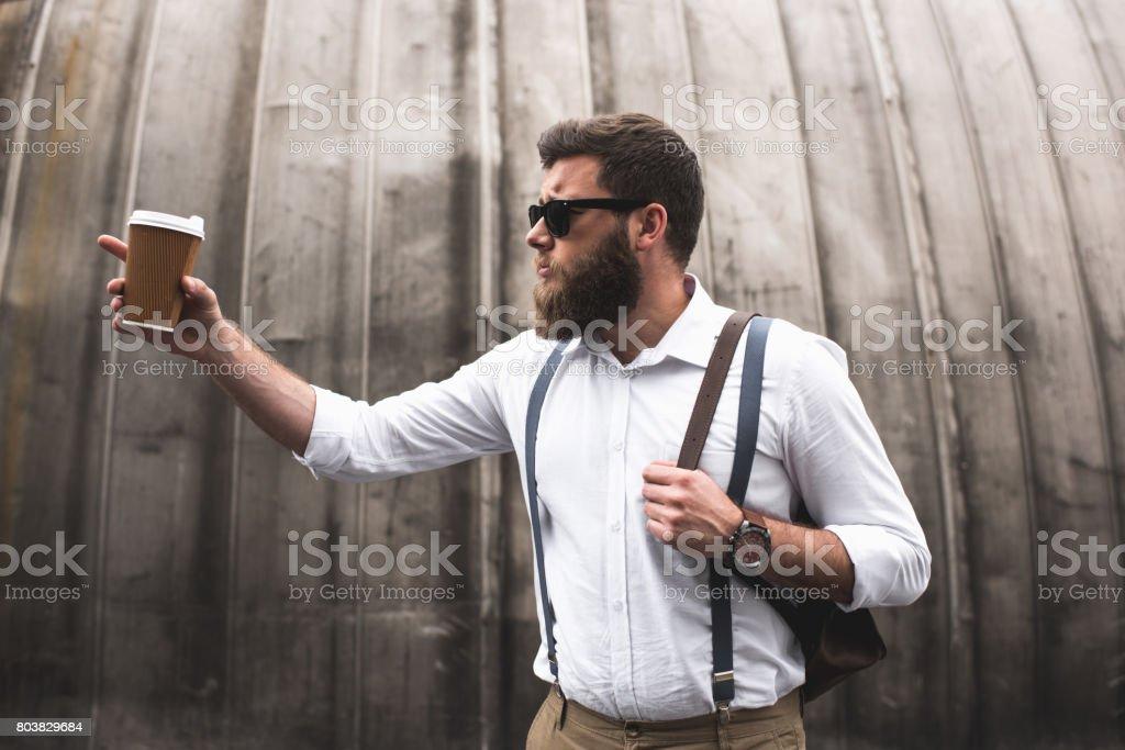c830d1b26 elegante barbudo homem com óculos de sol e mochila de couro segurando a  xícara de café