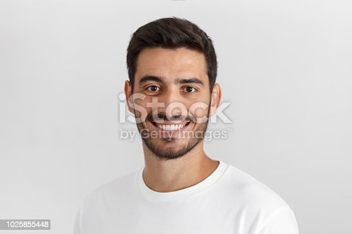 Stylish bearded man with trendy haircut smiling to camera, having pleased expression and cheerful look. Positive emotions concept.