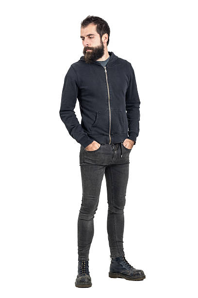 Stylish bearded punker wearing worn old leather boots looking down. Stylish bearded punker wearing worn old leather boots looking down. Full body length portrait isolated over white studio background. men in tight jeans stock pictures, royalty-free photos & images