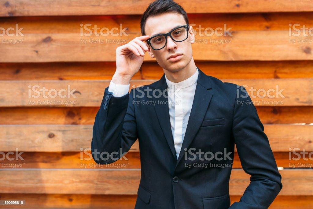 Stylish, beautiful, man in classic costume , posing near wooden wall. stock photo
