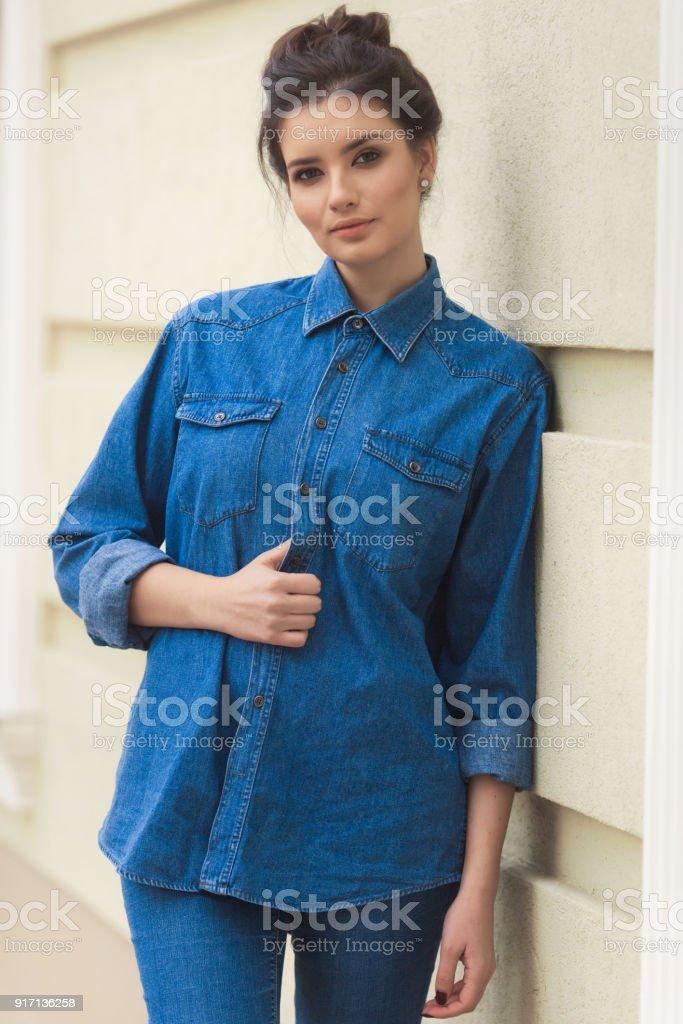 588ea1ee6 Elegante mujer bella camisa de dril de algodón había situado junto a la  pared. Calle
