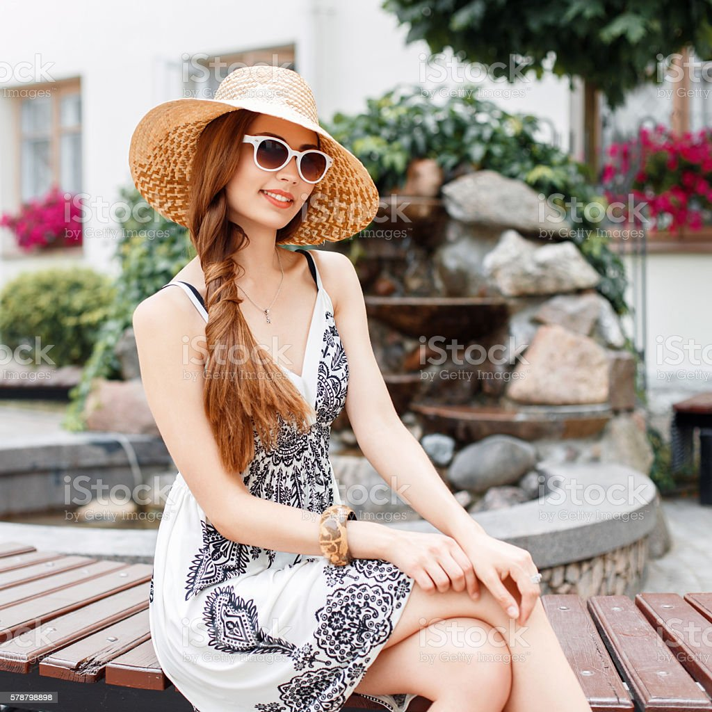 Stylish beautiful woman in summer clothes resting on a bench stock photo