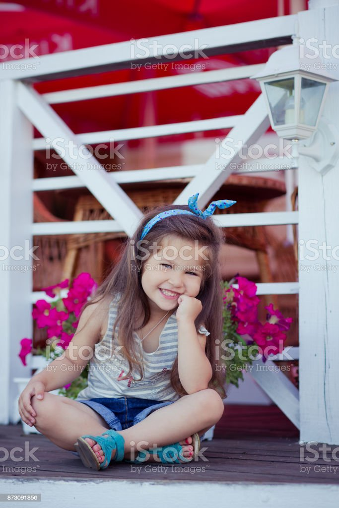Stylish beautifull cute baby girl with brunette hair posing on wooden garden full of flowers wearing tiny jeans shirts and airy skivy underwaist and blue sandals stock photo