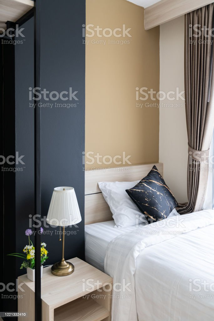Stylish Bedroom Corner With Wooden Headboard And Bed With Soft Pillows Setting With Navy Blue And Yellow Painted Wall On The Background Cozy Interior Design Modern Interior Stock Photo Download Image