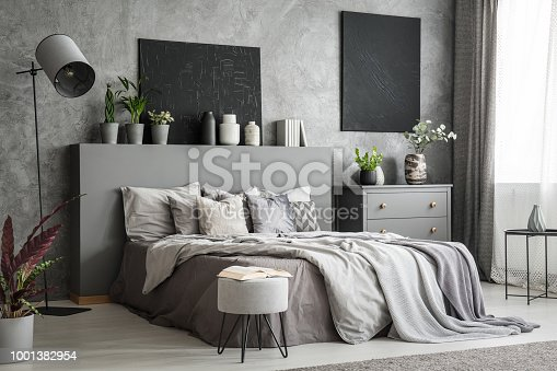 istock Stylish bedroom interior in grey with a big bed with bedsheets, pillows and blankets. A drawer cabinet and a standing lamp against a wall with black paintings. Real photo 1001382954