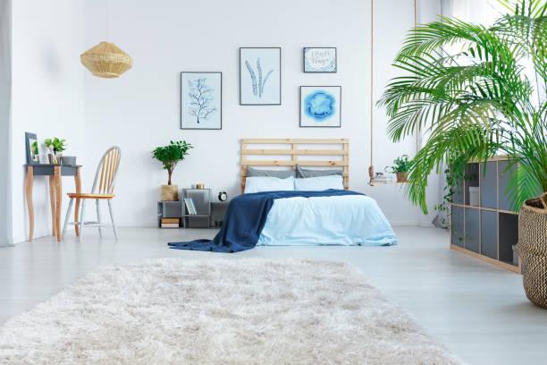 stilvolle schlafzimmer mit holzbett - marineblau schlafzimmer stock-fotos und bilder